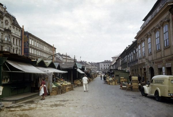 View of a street market in Vienna, Austria. There are wooden crates piled up on both sides of the road, and stalls with produce on display. A stallholder on the left is adjusting her sun blind. Date: 1953