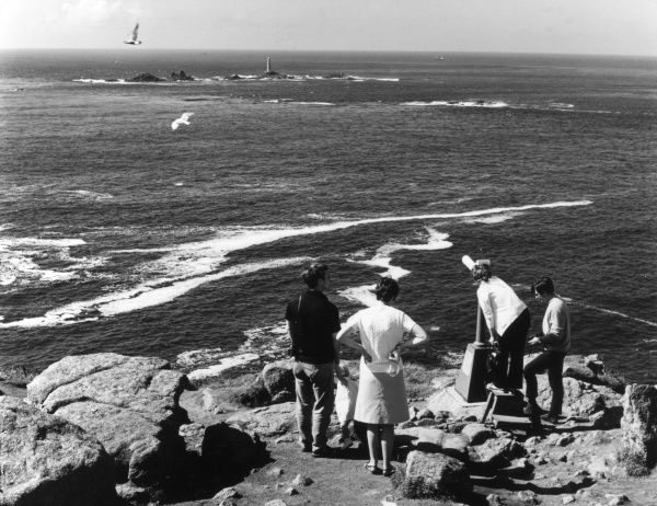 A family looking out to sea at Longships Lighthouse, using some 'pay' binoculars, Land's End, Cornwall, England. Date: 1960s