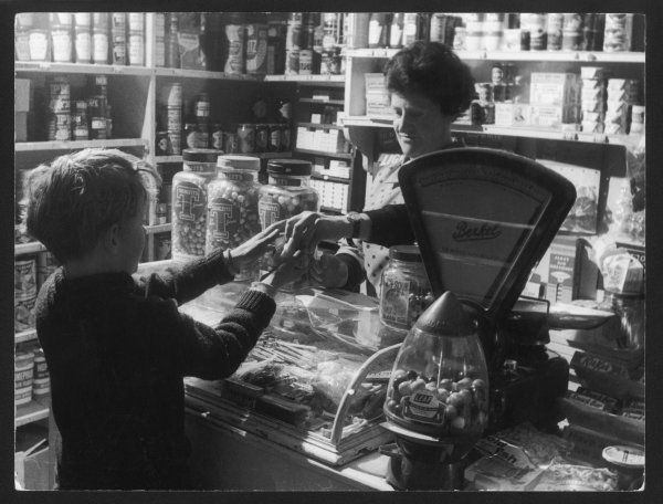A young boy being served in a well-stocked village shop, including sweets in jars, Homepride flour, Kit-Kat chocolate bars etc