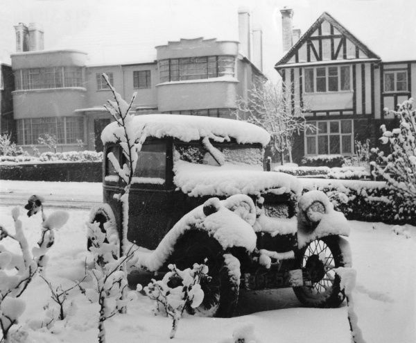 A vintage car covered in snow. Anyone fancy helping to crank start it?