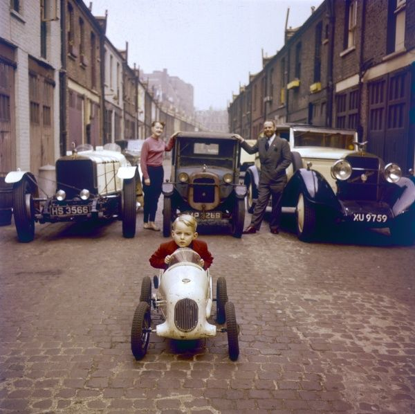 A little boy sits proudly in his model car, in front of three vintage cars parked on a cobbled street. Date: 1950s