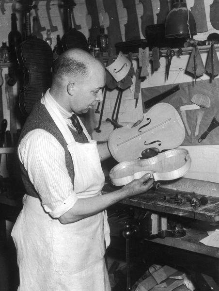 A violin maker fixing the wooden front onto the main body of the instrument in his workshop