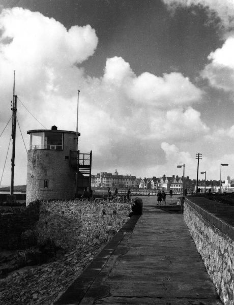 The view along the breakwater and the Coastguard's Lookout, at Porthcawl, Glamorganshire, Wales. Date: 1960s
