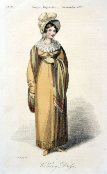 A long sleeved earth coloured gown (or possibly a pelisse worn over a gown) with a triple tier ruff. It is Worn with a green & red shawl and a bonnet with plumes