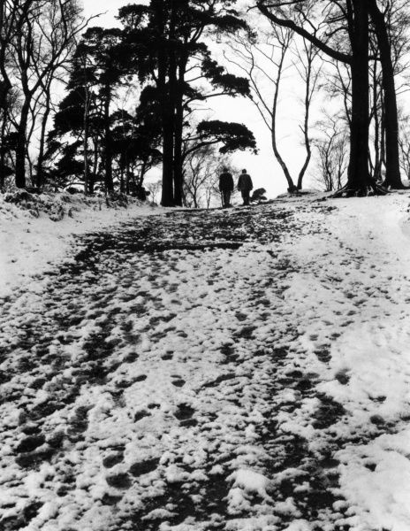Two people walking in the snow at Alderley Edge, Cheshire, England. Date: circa 1960