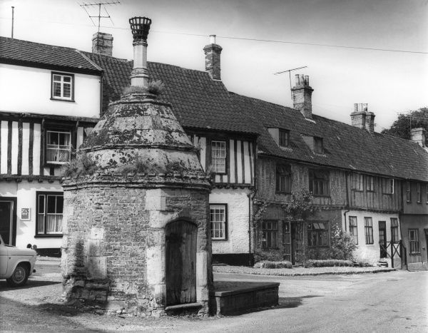 The old village pump, with its brick-built housing at Walsingham, Norfolk, England. Date: 1960s