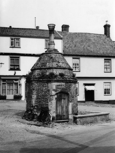 The ancient water pump in the town centre of Walsingham, Norfolk, England. Date: 1940s