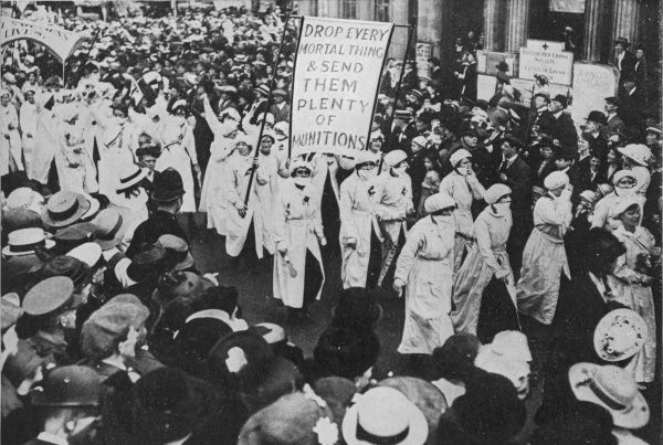 A photograph showing a procession by the Women's Social and Political Union. The group that can be seen wearing face masks are a party of female munition workers