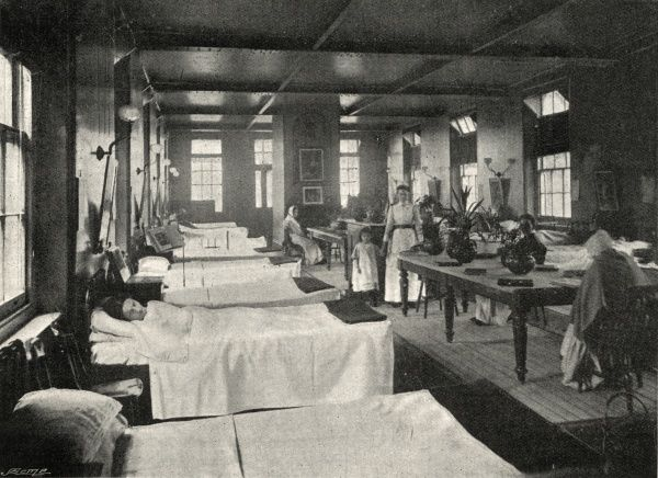 A ward in the Wandsworth & Clapham Union infirmary, St John's Hill, south west London. The room is decorated with potted plants and pictures. The floor is bare apart from a strip of matting. Originally opened in 1840 as the Wandsworth workhouse