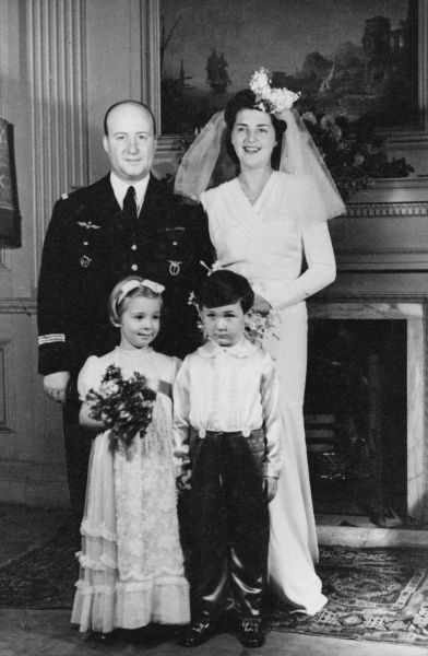 A wartime wedding group, with the groom wearing his air force uniform. The happy couple pose with their pageboy and bridesmaid