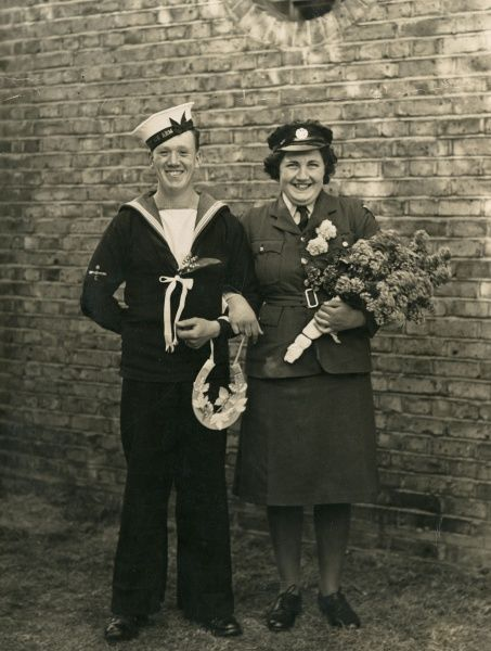 A wartime wedding, with both the bride and the groom in their respective uniforms. Date: circa 1940
