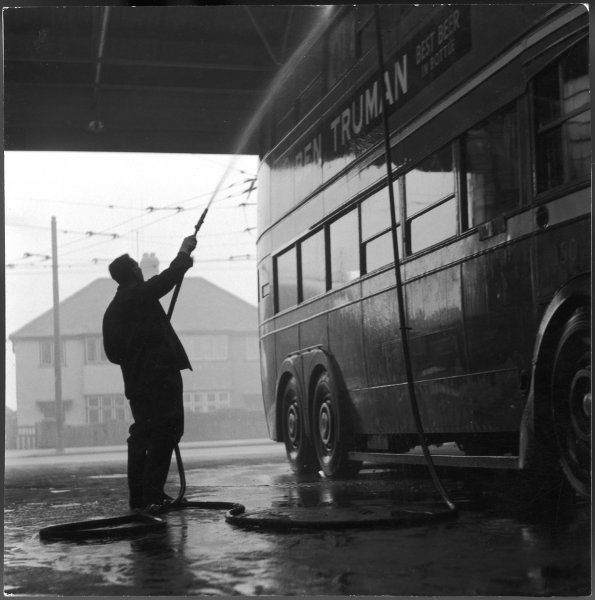 A man hosing down a bus in the bus depot