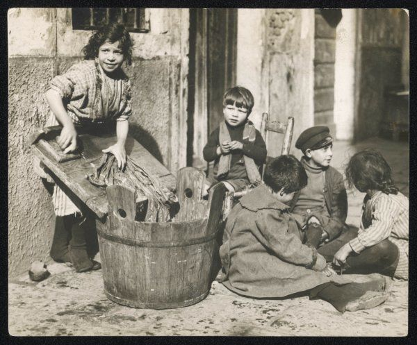 Poor children of Castello, Italy, doing the family laundry on washing day