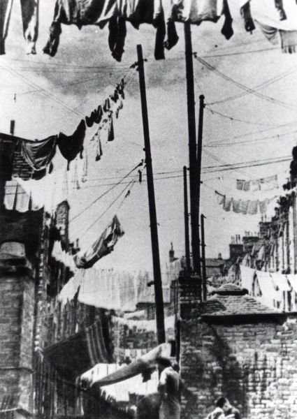 Numerous washing lines with clothes hanging out to dry at the back of terraced housing in an unidentified mining area of South Wales