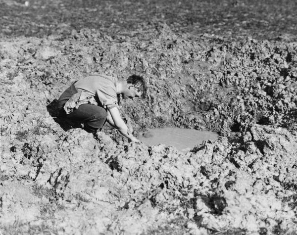 A British soldier washing in a shell hole in France on the British front during World War I on 21st April 1917