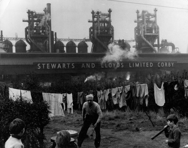 A washing line and an old man and children in the back garden of a house backing onto the 'Steward & Lloyds' steel mill, Corby, Northamptonshire, England. Date: late 1960s
