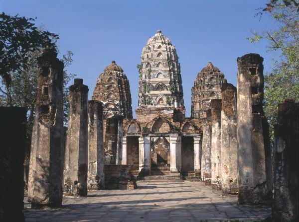 View of Wat Sri Sawai, a small Buddhist temple with three prangs in Old Sukhothai, Thailand. There are many Hindu images and scenes here, suggesting that Sri Sawai was first a Hindu temple, and was later converted to a Buddhist monastery
