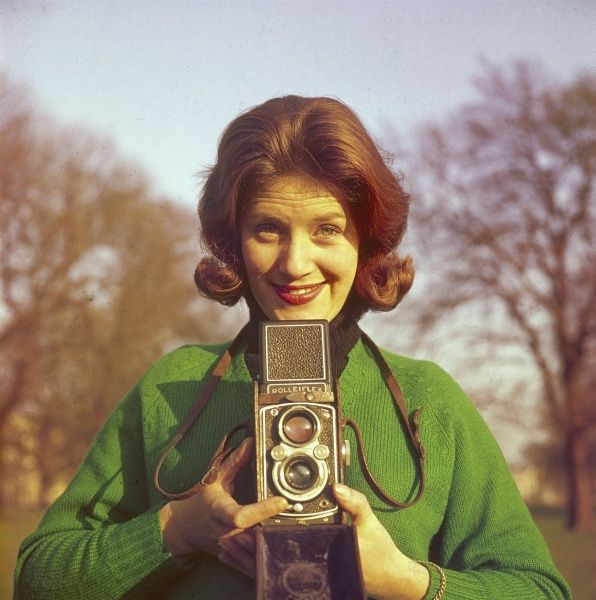 'Watch the Birdie!' A female photographer adjusts her camera lens in a park, ready to capture her subject - YOU! Date: 1960s