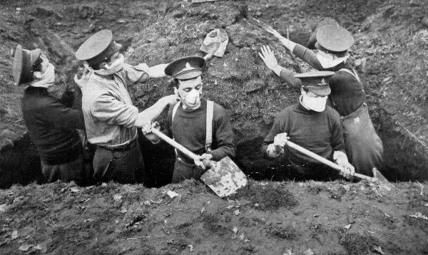 Photograph of British soldiers wearing respirators while digging a trench to guard against fumes from bursting shells. The Germans first used poison gas at Ypres on 22nd April 1915