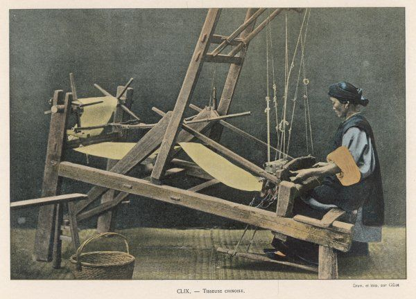 A woman working at a large wooden framed loom in China