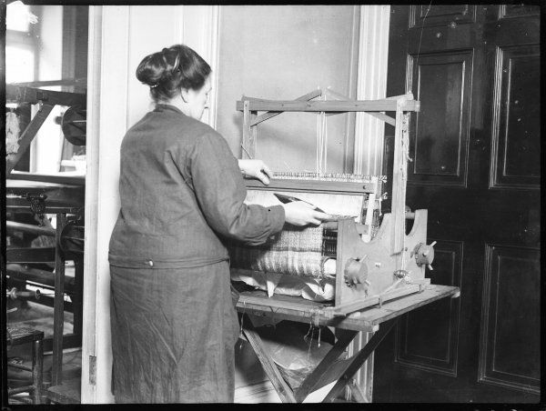A woman using a table hand loom, which apparently can weave anything in any type of pattern