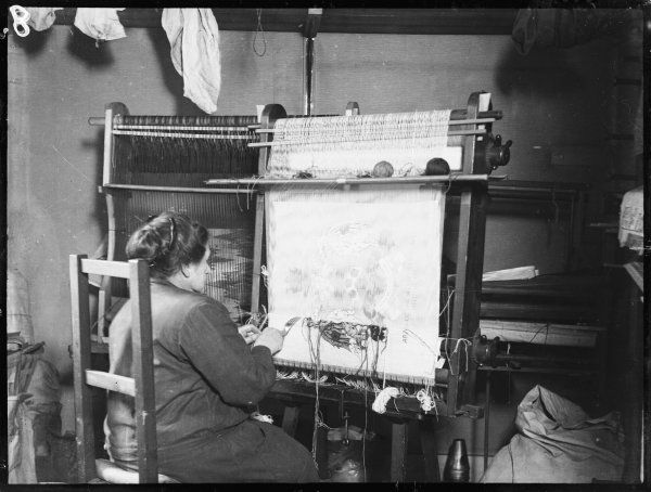 A woman weaving a tapestry of 'Arms of the Weavers of London 1700' on a wooden hand loom