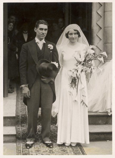Newly-wedded couple in formal dress, he with a buttonhole, she with a bouquet