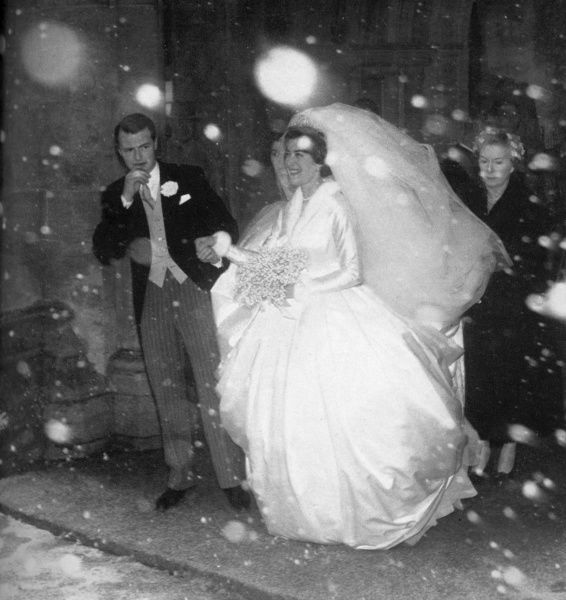 Lady Pamela Mountbatten (born 1929), younger daughter of Lord Louis Mountbatten, emerging with her groom, David Hicks (1929 - 1998) from Romsey Abbey during a snowstorm on their wedding day, 13th January 1960. Date: 1960