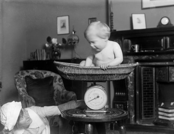 A nurse weighing a baby in a wicker basket on a set of weighing scales. Date: 1930s