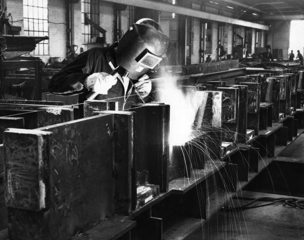 Sparks fly as a welder works on huge metal blocks in a factory in Middlesbrough, Teesside, England. Date: 1960s