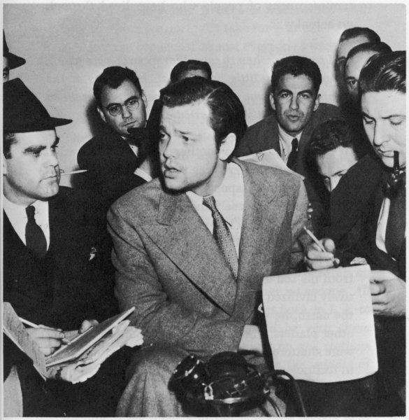 Orson Welles speaks with newsmen, 30 October 1938, after the sensational broadcast of a dramatised version of the book by the Mercury Theatre, NY