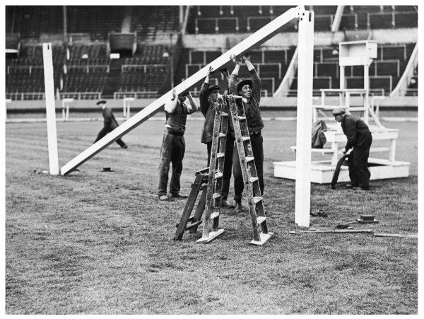 Workmen fixing goal posts at Wembley Stadium two days before the 55th F.A. Cup Final, when Aresenal defeated Huddersfield Town (2-0), in front of a 98,488 crowd
