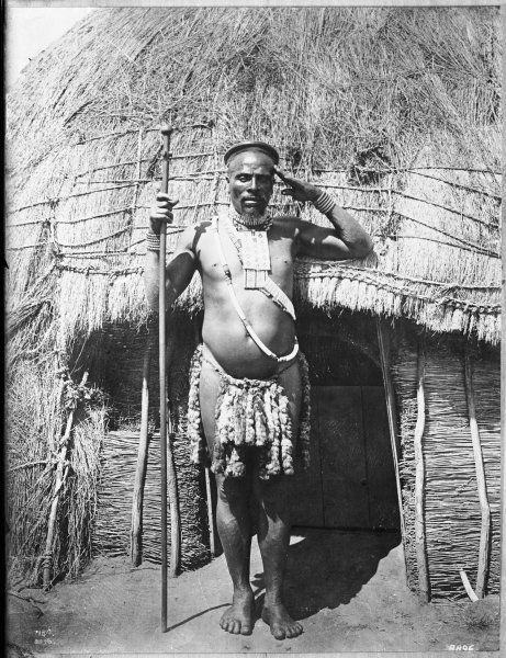 A West African native sentry stands to attention and salutes outside the entrance to a hut