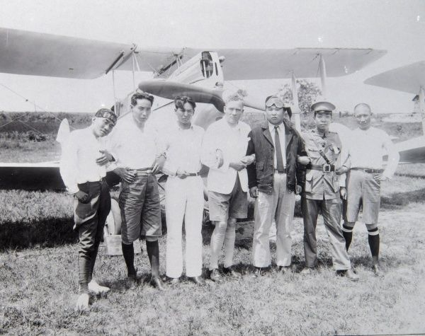 Western aviator on a trip to the Far East, in a field with his hosts, posing for their photo in front of the aircraft