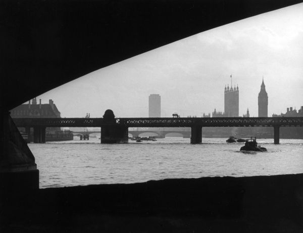 Evening view looking towards the Houses of Parliament, Westminster, London, from below Waterloo Bridge. Date: 1950s