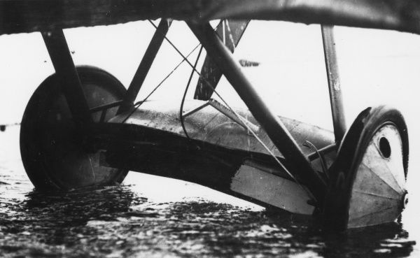 The wheels of a plane partially submerged in a muddy field during the First World War. Date: 1914-1918