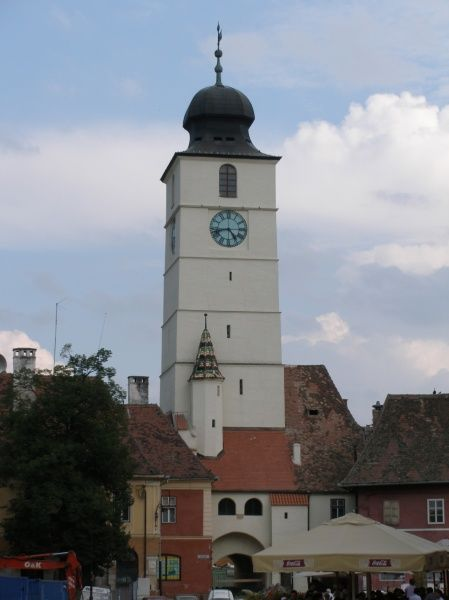 View of the white clock tower on the small square (Piata Mica) in Sibiu, Transylvania, Romania. The tower is known as the Turnul Sfatului (the Tower of the Council), and was built in the 13th century