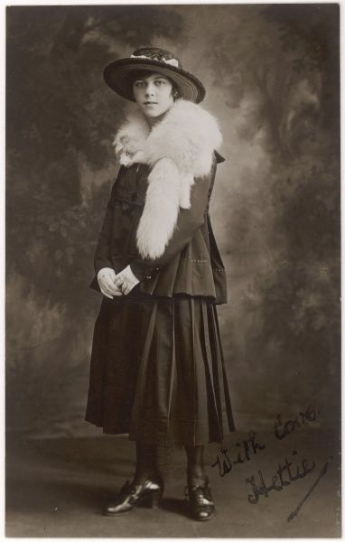 A girl in clothing typical of the Great War period wears a white fox fur stole, complete with head, tail & feet, around her shoulders. Date: circa 1917