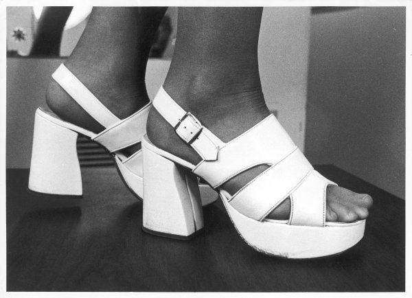 A close-up photograph of feet in a pair of white platform sandals