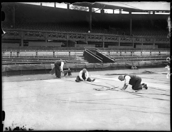 In preparation for the annual All England Lawn Tennis Championships, Wimbledon, sailmakers repair the tarpaulin used to cover Centre Court, should rain stop play