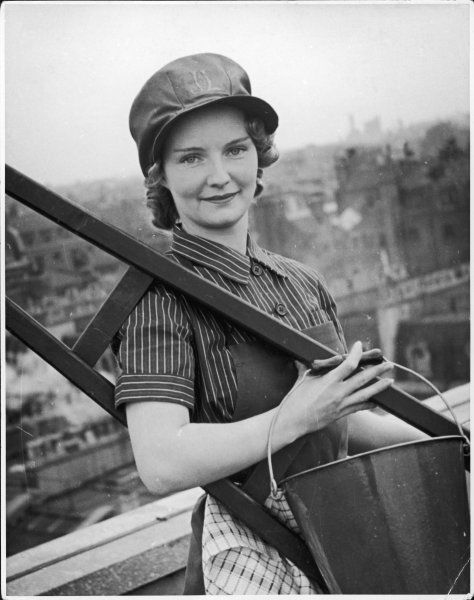 Georgina, replaces the male window cleaner whilst he is in the army during World War Two. She wears an apron, a ladder on her shoulder and a bucket over her capable arm
