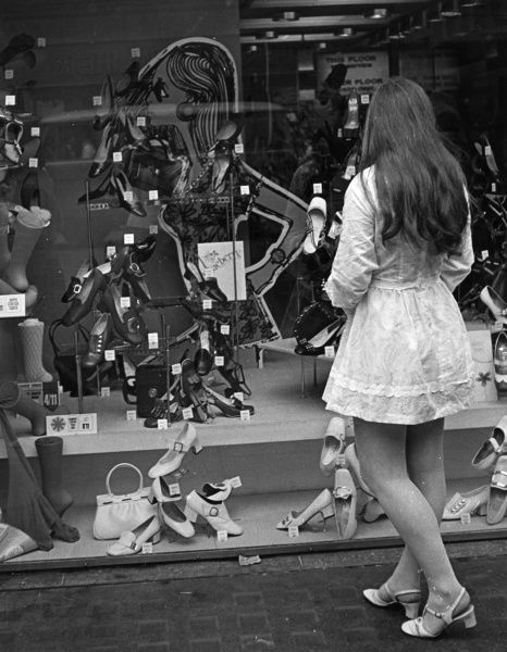 A brunette in a mini dress and slingbacks, staring longingly at all the shoes on display in a shoe shop window... Date: late 1960s