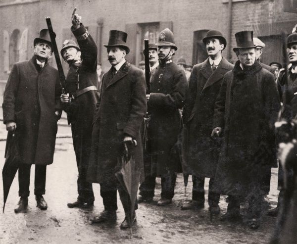 Winston Churchill, then Home Secretary, together with policemen and civilians, during the Sidney Street Siege (popularly known as the Battle of Stepney) in East London