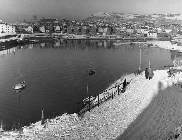 Winter sunshine after snow, a scene by the harbour at Aberystwyth, Wales. Date: 1950s