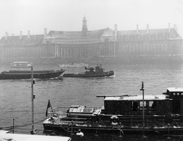 Winter in London : A view from Westminster Pier, showing County Hall and industrial barges on the River Thames during a snowstorm. Date: 1950s