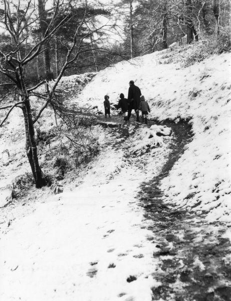 A father takes his children for a country walk in the winter snow. Date: 1960s