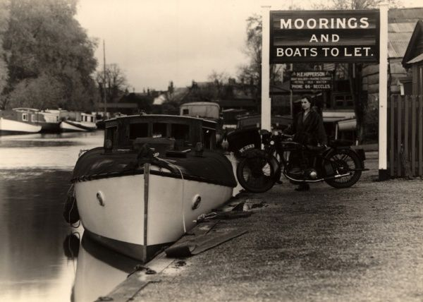 A woman poses with a motorbike alongside a boat moored at Captain Bloomfield's Moorings at Beccles in Suffolk, East Anglia