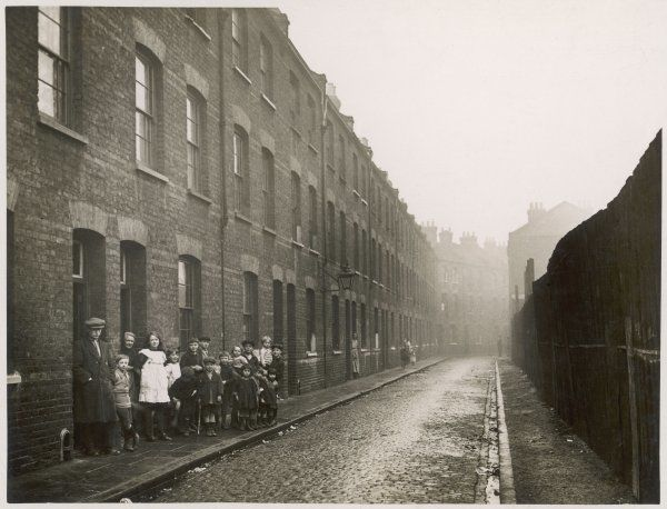 A street, possibly Bethnal Green, and some of its dwellers who gather for a group photograph on the pavement