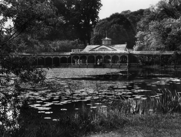 The Chinese Dairy at Woburn Abbey, seat of the Duke of Bedfordshire, England, seen from across the beautiful water lily pond, noted for its tame fish, surfacing for food. Date: 1950s