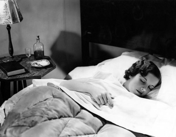 A young woman sleeps peacefully in bed Date: 1930s
